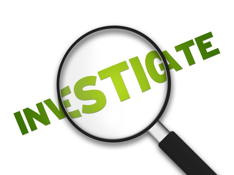 Magnifying Glass with the word Investigate on white background.